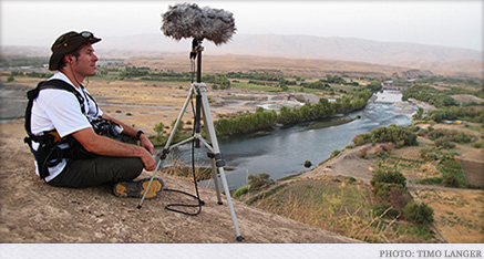 Brent Calkin surveying the Kurdistan landscape with his sound equipment by his side.