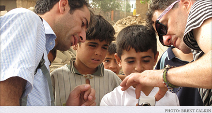 Gharib Rauf Ahmad helping Mark show some Kurdistani children how to use a little video camera.
