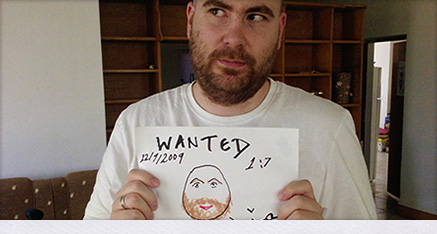 Timo Langer looking coy holding an arabic 'wanted' poster of himself (drawn in felt tip).